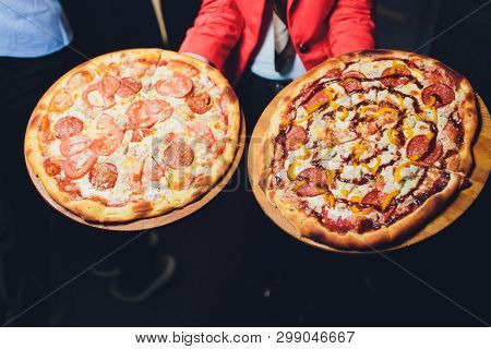 Waiter Carrying Two Different Plates With A Tasty Pizza. Photo With Two Pizza. Pizza With Mushrooms