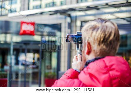 Germany, Munich - December 26, 2018: Man Blogger Shooting Video On Smartphone Iphonexs Using An Imag