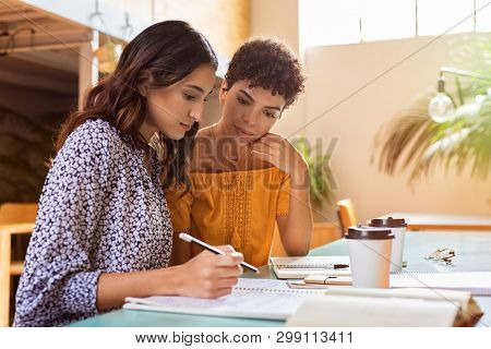 Young multiethnic women studying together at library. High school or college students studying and reading together in cafeteria. Latin girl explaining to brazilian friend the lesson.