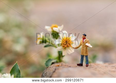 Miniature People : Artist Holding A Brush And Painting Flower In The Garden