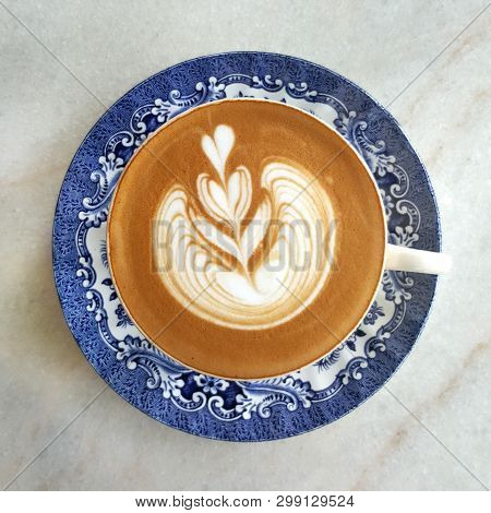 Top View Of A Mug Of Latte Art Coffee In An Antique Cup On White Marble Background.