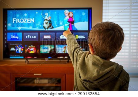 Barcelona, Spain. May 2019: Back View Image Of Cute Little Boy Watching The New Disney Plus Platform