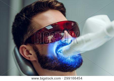 Teeth Whitening. Man Having Teeth Whitened By Dental Uv Laser Whitening Device. Teeth Whitening Mach