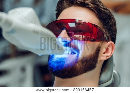 Man Having Teeth Whitening By Dental Uv Whitening Device,dental Assistant Taking Care Of Patient,eye