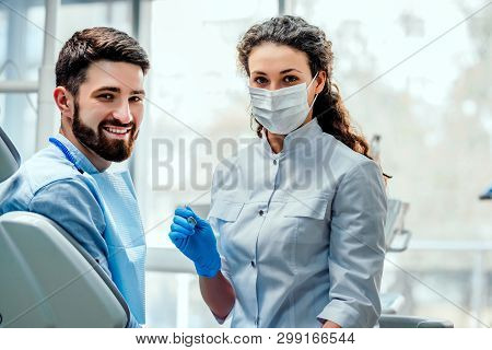 View Of A Young Attractive Dentist Explaning His Work To A Patient.