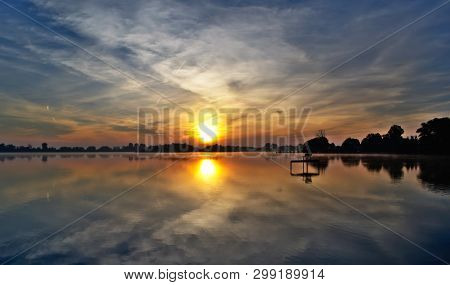 A Phenomenal Play Of Light In The Sky And In The Water During The Sunrise Over Lake Kunice In Poland