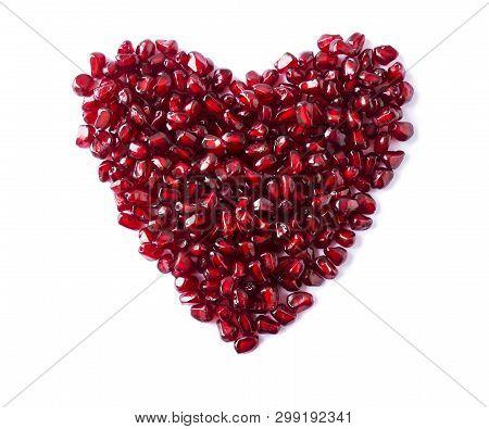 Heart Shape Pomegranate Seeds On White Background. Background Made Of Red Pomegranate Seeds. The Sca
