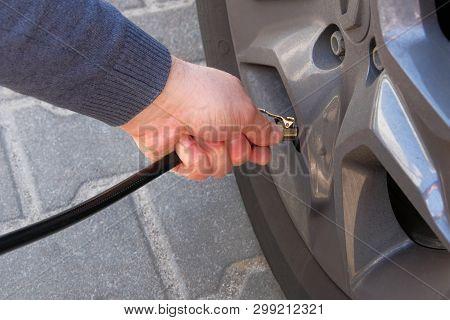 Car Service. Man Checks Pressure In Car Tires. Hand On Auto Tire. Automobile Maintenance Concept.