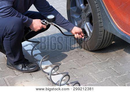 Car Service. Man Checks Pressure In Car Tires. Hand On Auto Tire Valve. Automobile Maintenance Conce