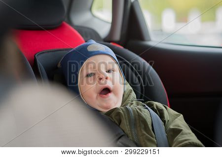 Close Up Caucasian Cute Baby Boy Woke Up And Yawns In Modern Car Seat. Child Traveling Safety On The