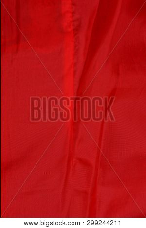 Red Fabric Texture From A Piece Of Crumpled Cloth On Clothes