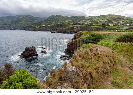 Green Coastline With Dark Clouds In The Background Above Ponta Delgada On The Island Of Flores In Th