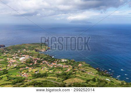 Ponta Delgada In The Summer Sun With Corvo Island In The Distance.