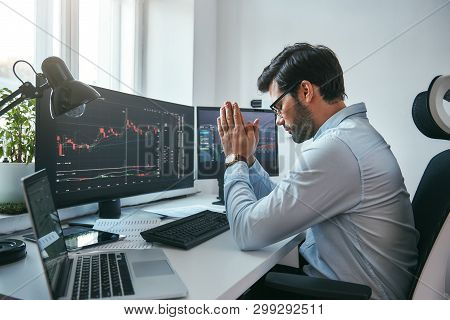 Hoping for the success. Side view of tired young businessman or trader holding palms together while working with data and charts on computers at his modern office. poster