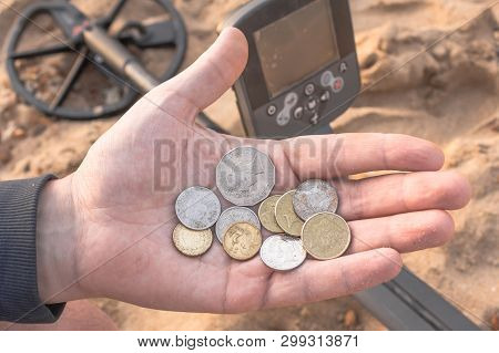 Searching With Metal Detector On The Beach
