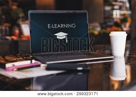 Close Up Of Laptop With Inscription On Screen E-learning And Image Of Square Academic Cap On Table I