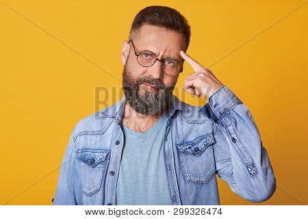 Close Up Portrait Of Smart Handsome Middle Aged Caucasian Man Thinks With Finger On Head Isolated On