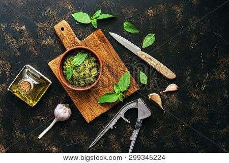 Pesto Sauce In A Clay Bowl, Basil Leaves And Garlic On A Dark Background, Top View. Mediterranean Sa