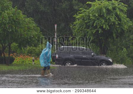 Red Car Rides In Heavy Rain On A Flooded Road