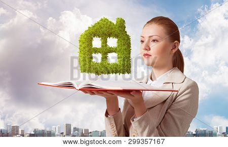 Woman With Green Plant Shaped House Above Opened Notebook. Real Estate Agency Advertising. Sale New