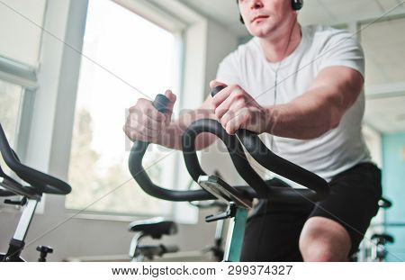 Healthy Lifestyle Concept. Young Sporty Man In White T-shirt And Shorts Is Exercising Bike At Spinni