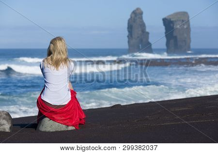 Beautiful Blonde Woman Sits On Beach Stone, Near To The Iconic Wild Rock Formations Next To Mosteiro