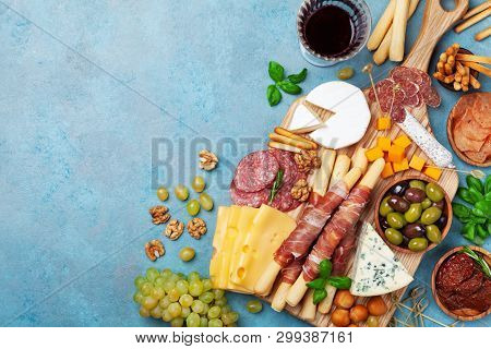 Italian Appetizers Or Antipasto Set With Gourmet Food On Blue Table Top View. Mixed Delicatessen Of