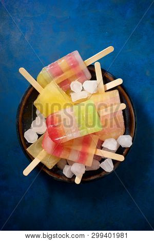 Popsicles on a blue table.