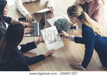 Businesswoman in group meeting discussion with other businesswomen colleagues in modern workplace office with laptop computer and documents on table. People corporate business working team concept. poster