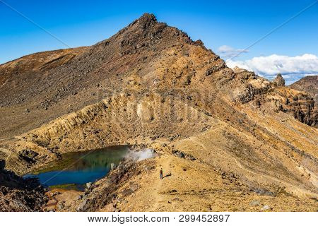 New Zealand Tongariro Alpine Crossing National Park. Tramping tramper hiker man walking on famous destination in NZ. Popular tourist hiking hike hero view of landscape.