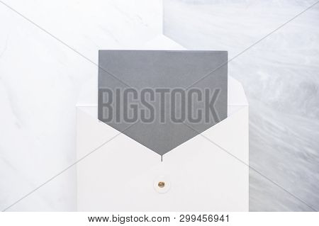 Top View Of Blank Grey Card In White Envelop On Two Layer Step Of Marble Table Top.mock Up Template