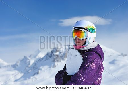 Woman holding snowboard with mountains in background. No brandnames or copyright objects.
