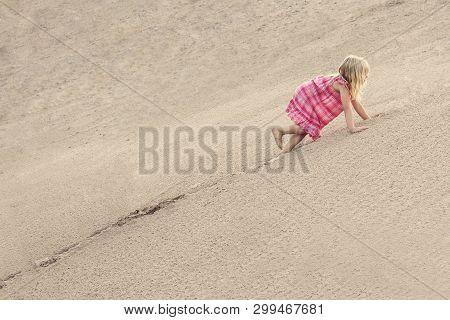 Girl Climbing On The Sand Dune. Summer Day