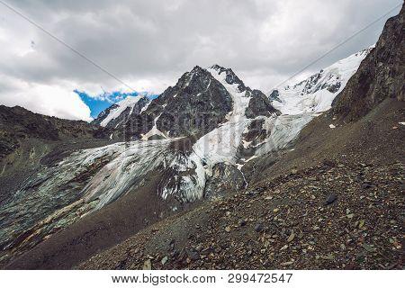 Snowy Giant Mountain Range Under Cloudy Sky. Rocky Ridge With Snow. Huge Glacier. Icy Mountainside W