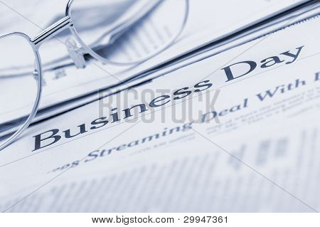 Eyeglasses Lie On The Newspaper With Title Business Day. Blue Toned