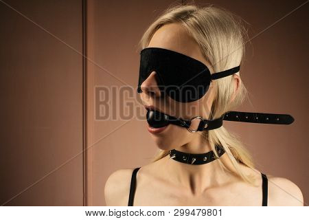 Sexy Lady In Bdsm Outfit. Close-up Girl In Mask And Collar With Gag In Mouth -image