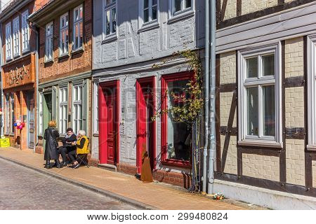 Schwerin, Germany - April 16, 2019: People Sitting In The Sun In Front Of Their  Colorful Houses In