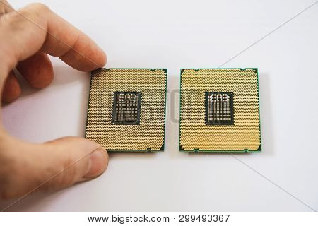 Man hand comparing two new powerful workstation CPU processors before service new computer workstation server poster