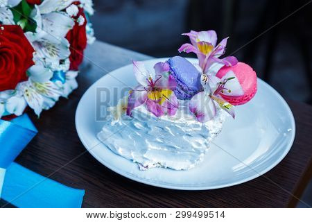 Piece of Festive Cake decorated flowers and cream on table near the bride's bouquet