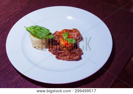 roast meat with potatoes on white plate