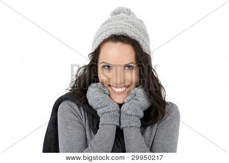 Winter portrait of happy woman, posing in scarf, cap and gloves, smiling at camera.?
