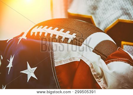 American Football Concept. The Ball For American Football Lies On The Flag Of America Against The Ba