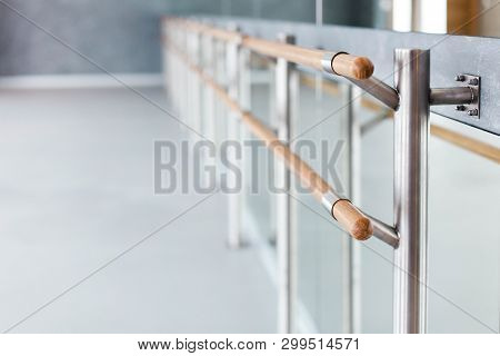 Ballet Wooden Barre By Mirror In Dance Class Room. Blurred Background Of Ballet Modern School.