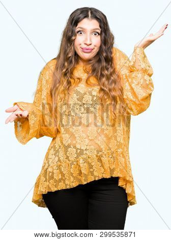 Young beautiful woman wearing yellow elegant dress clueless and confused expression with arms and hands raised. Doubt concept.