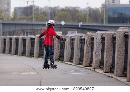St. Petersburg, Russia - May 02, 2019:  A Little Girl In A Red Jacket And Blue Jeans On Rollers And