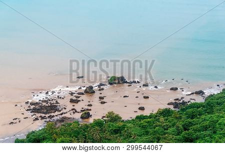 Rocky Soft Pastel Blue Beach Near The Forest. Calm And Serenity Blue Coastline Mix With Muddy Sedime