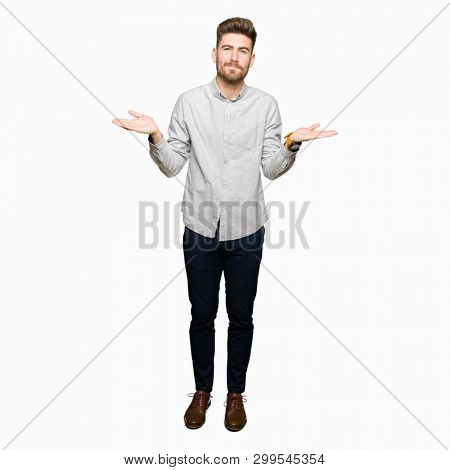 Young handsome man wearing casual shirt clueless and confused expression with arms and hands raised. Doubt concept.