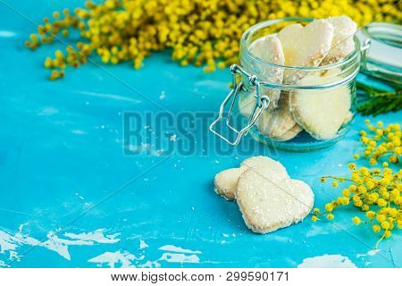 Delicious Baked Heart Shaped Cookies With Coconut Chips In Glass Jar And Fresh Silver Wattle Or Mimo