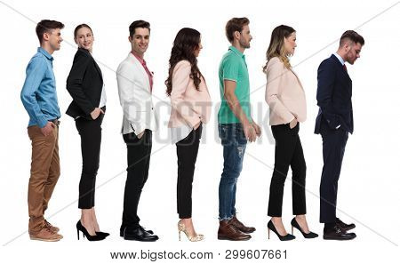 curious businessman looks down at something while witing in line with other young people
