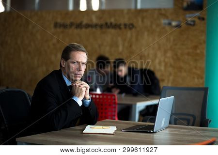 Thoughtful Businessman Sitting At Desk In Office. Having Laptop Nearby. Business In Office Concept.